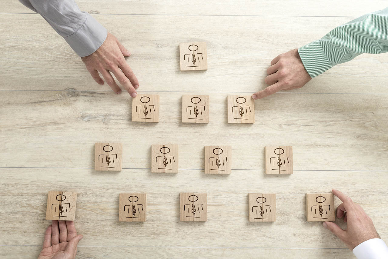 Pyramid of figures on wooden blocks with the hands of businessmen reaching out to touch four of them in a teamwork and human resources concept.